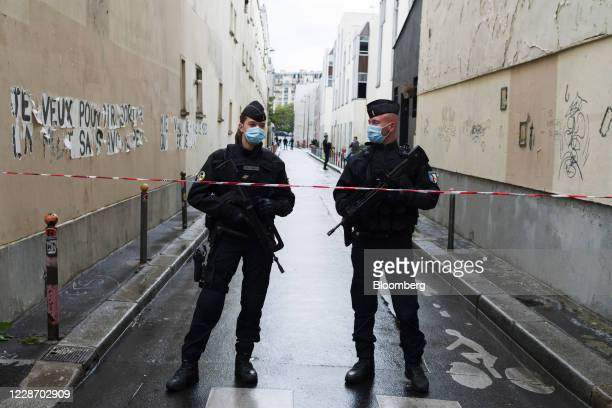 Police officers stand guard in a cordoned off side street following reports of a knife attack in Paris, France, on Friday, Sept. 25, 2020. Four...