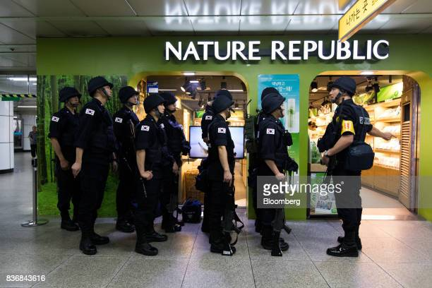 Police officers stand guard in front of a Nature Republic cosmetics store during an antiterror drill on the sidelines of the Ulchi Freedom Guardian...