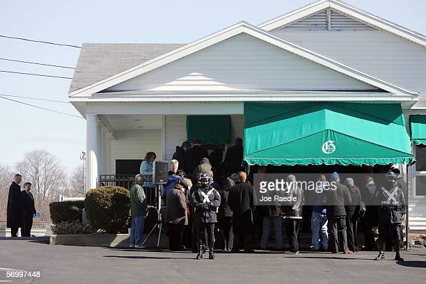 Police officers stand guard in front of a small overflow crowd of mourners listening to the service on speakers set up outside the Gormley Funeral...