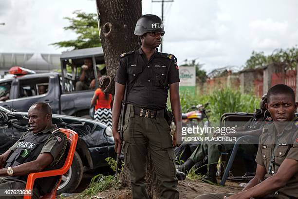 Police officers stand guard in front of the Independent National Electoral Commission offices in the oil hub of Port Harcourt as election materials...
