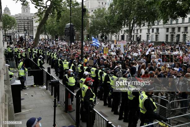 Police officers stand guard in front of the No 10 Downing Street as opponents of the new type of coronavirus measures, environmentalists and...