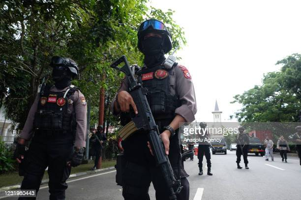Police officers stand guard in the front of the Sacred Heart of Jesus Cathedral after a suicide bomb attack in Makassar, South Sulawesi province,...