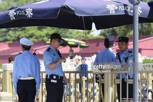 Police officers stand guard in Tiananmen Square on the anniversary of the 1989 crackdown on democracy protestors in Beijing on June 4 2018 Hundreds...