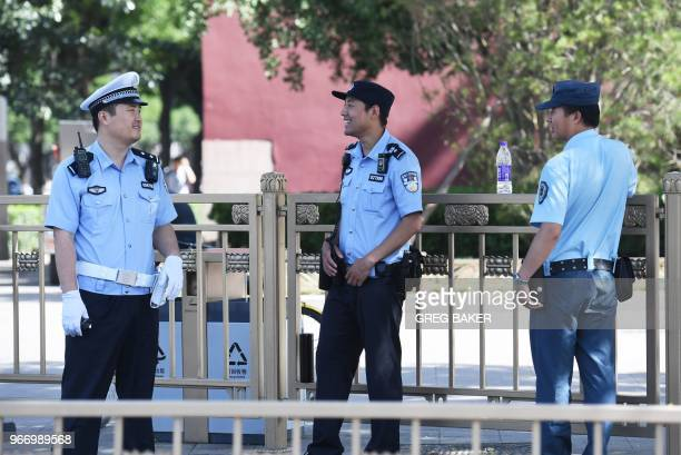 Police officers stand guard near Tiananmen Square on the anniversary of the 1989 crackdown on democracy protestors in Beijing on June 4 2018 Hundreds...