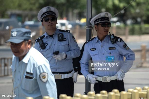 Police officers stand guard near Tiananmen Square on the anniversary of the 1989 crackdown on democracy protestors in Beijing on June 4 2018 Open...