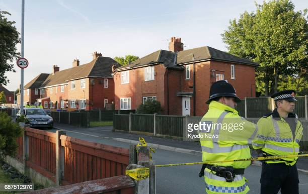 Police officers stand guard on May 23 near the house of Salman Abedi suspected suicide bomber in Manchester England following an explosive attack on...