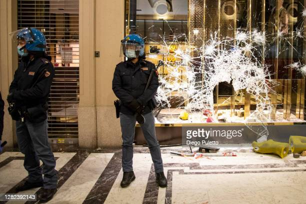 Police officers stand guard outside a Gucci boutique store as protesters gather during an anti government demonstration on October 26 2020 in Turin...