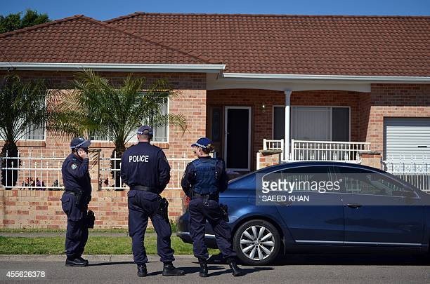 Police officers stand guard outside a house during a raid in the Guildford area of Sydney on September 18 2014 Australia's largest ever...