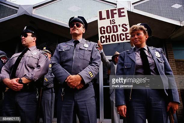 Police officers stand guard outside a women's clinic in Buffalo during an antiabortion protest A prolife demonstrator holds up a sign that reads...