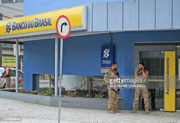 Police officers stand guard outside the bank which robbers struck just after midnight, in Criciuma, Brazil, on December 1, 2020. - A group of 30...