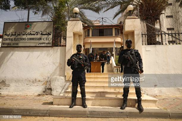 Police officers stand guard outside the Central Elections Commission's office in Gaza City on March 20 at the start of the registration period for...