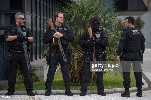 Police officers stand guard outside the Federal Police headquarters where former Brazilian president Luiz Inacio Lula da Silva is awaited to start...