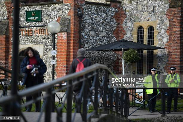 A police officers stand guard outside The Mill pub close to The Maltings shopping centre in Salisbury southern England on March 8 2018 which was...