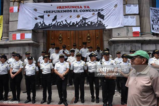 Police officers stand guard outside the National Congress during a protest against the government policies on the International Commission Against...