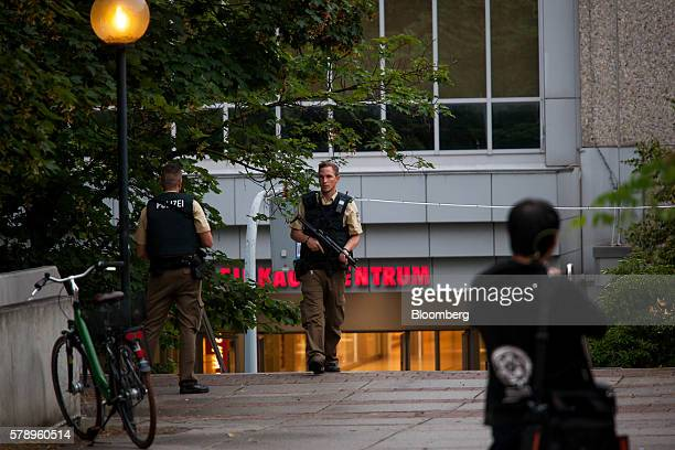Police officers stand guard outside the OlympiaEinkaufszentrum shopping center after a shooting in Munich Germany on Friday July 22 2016 German...