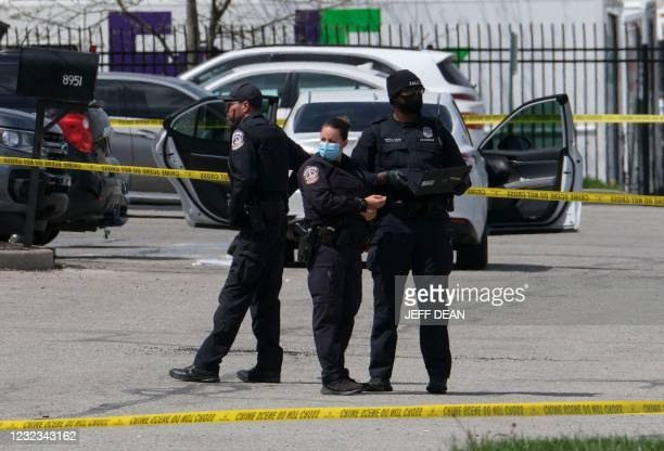 Police officers stand guard outside the site of a mass shooting at a FedEx facility in Indianapolis, Indiana on April 16, 2021. - A gunman has killed...