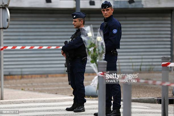 Police officers stand guard the street on July 27 2016 in SaintEtienneduRouvray 125 kilometres north of Paris where a priest was killed the day...