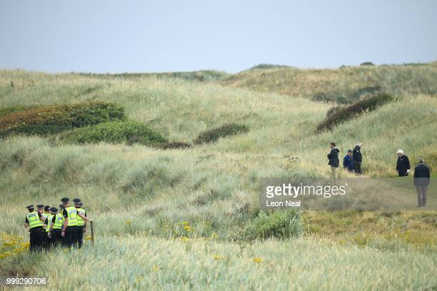 Police officers stand guard whilst US President Donald Trump plays a round of golf at Trump Turnberry Luxury Collection Resort during the US...