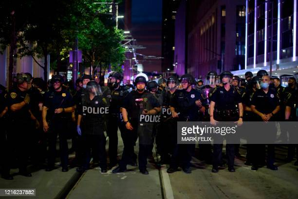 Police officers stand in a row during a Justice 4 George Floyd demonstration over the death of George Floyd a black man who died after a white...
