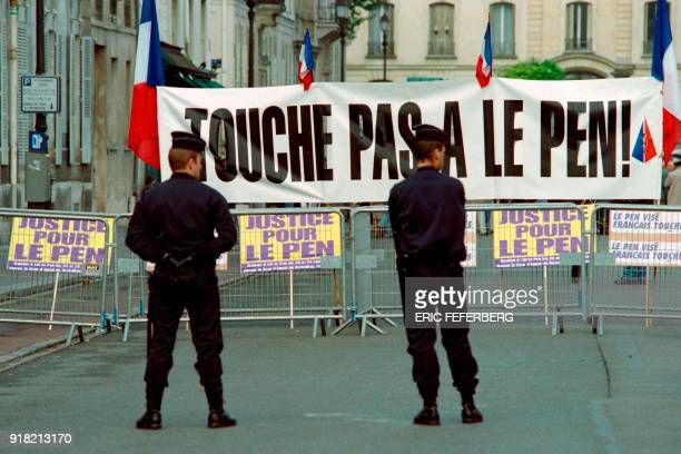 Police officers stand in front of a banner reading 'don't touch to Le Pen' during the trial of French National Front leader JeanMarie Le Pen at the...