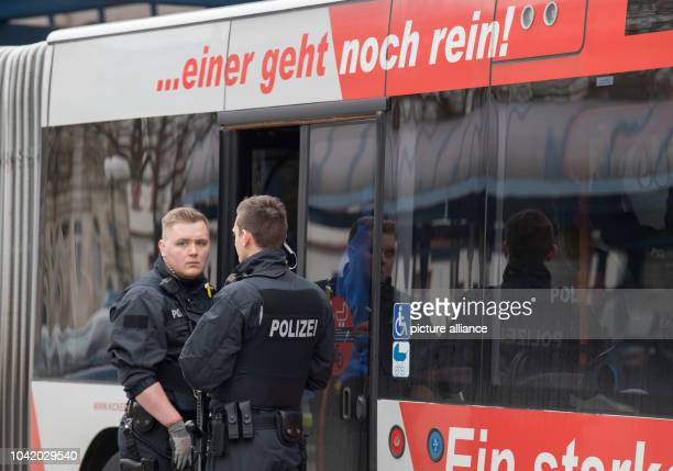Police officers stand in front of a bus during a control action against illegal passangers at the central bus station in Offenbach Germany 23 March...