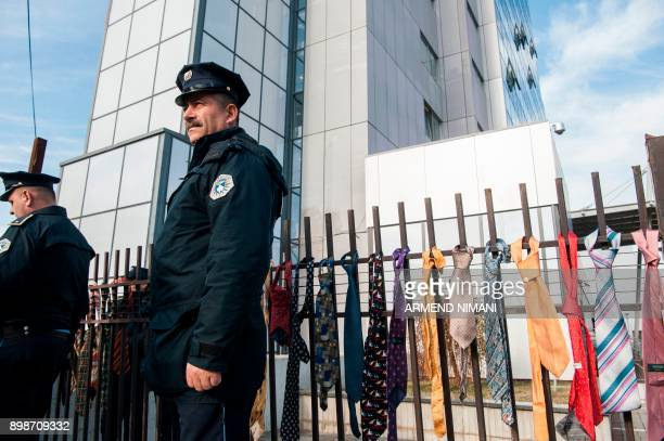 Police officers stand in front of a fence of the Kosovo government where ties were hanged in Pristina on December 26 2017 Around 300 ties were...