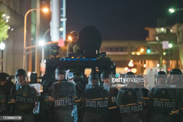 Police officers stand in front of an armored vehicle on September 23, 2020 in Louisville, Kentucky. Protesters took to streets after Kentucky...