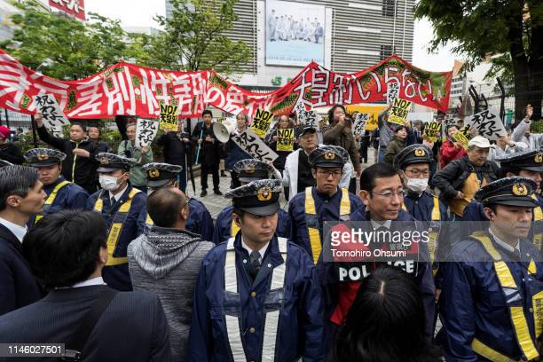 Police officers stand in front of demonstrators holding signs during a protest against Japan's Emperor system on April 30 2019 in Tokyo Japan Japan's...
