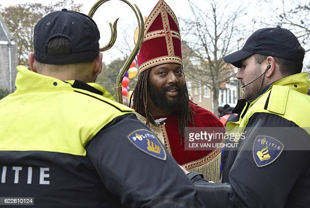 Police officers stand in front of Dutch actor Patrick Mathurin dressed up as the new ''Sinterklaas'' before the arrival of ''Sinterklaas'' in...