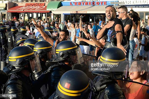 Police officers stand in front of Palestinian supporters shouting slogans and doing the quenelle gesture on the sidelines of a demonstration...