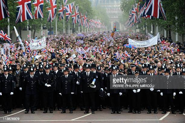Police officers stand in front of royal supporters on The Mall in London along the Processional Route in central London on April 29 2011 AFP PHOTO /...