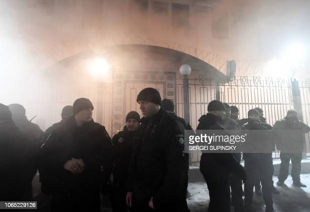 TOPSHOT Police officers stand in front of the Russian Embassy in Kiev late on November 25 while smoke from a flare thrown by protesters is seen...