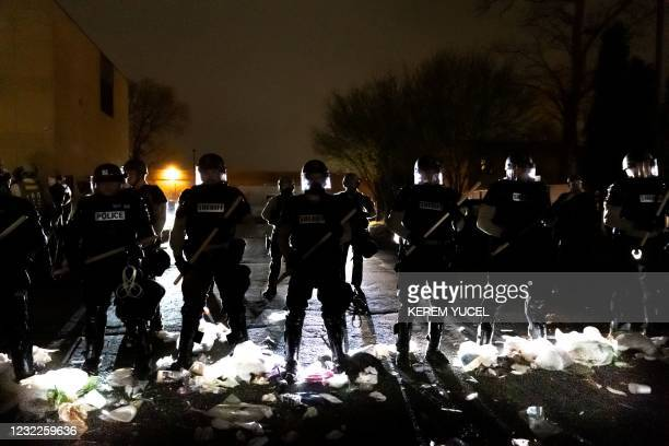 Police officers stand in line in front of the Brooklyn Center Police Station as people protest after an officer shot and killed a black man in...
