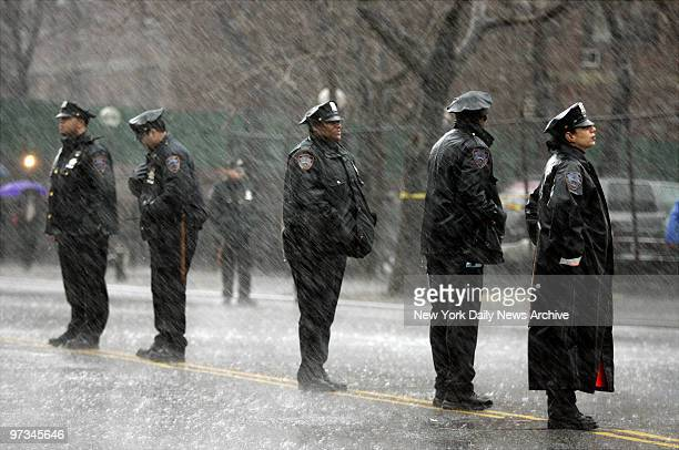 Police officers stand in the wind and driving rain outside St Mary's Church on Grand St where the funeral service for Nixzmary Brown was being held...