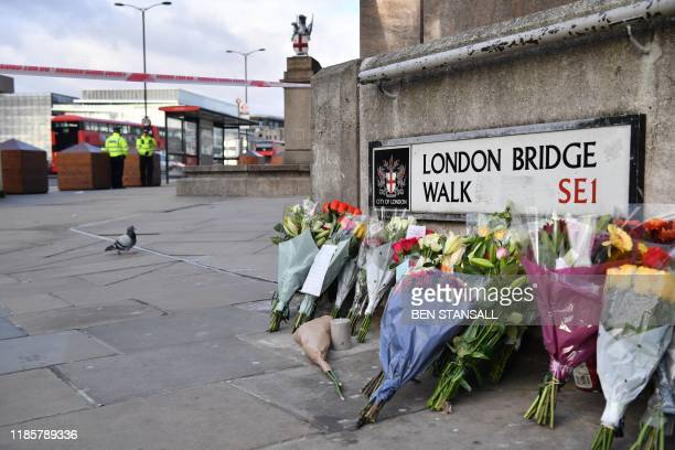 Police officers stand inside a cordon beside floral tributes left close to London Bridge in the City of London on December 1 following the November...