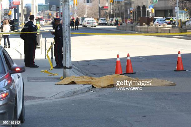 TOPSHOT Police officers stand near a body that is covered up after it was hit after a truck drove up on the curb and hit several pedestrians in...