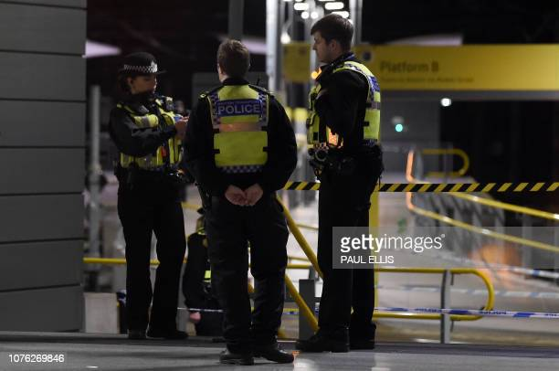 Police officers stand near a cordon at Manchester Victoria Station, in Manchester on January 1 following a stabbing on December 31, 2018. - A man, a...