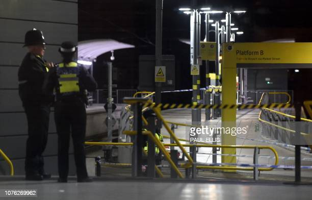 Police officers stand near a cordon at Manchester Victoria Station in Manchester on January 1 following a stabbing on December 31 2018 A man a woman...