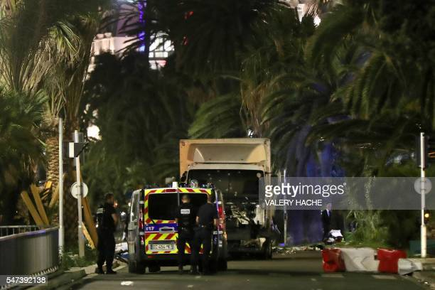 Police officers stand near a truck with its windscreen riddled with bullets that ploughed into a crowd leaving a fireworks display in the French...