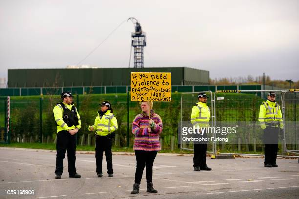 Police officers stand near an antifracking protester attempting to stop a tanker lorry leaving the Preston New Road drill site where energy firm...