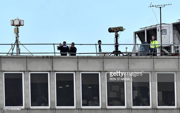 Police officers stand near equipment on the rooftop of a building at London Gatwick Airport south of London on December 21 as flights resumed...