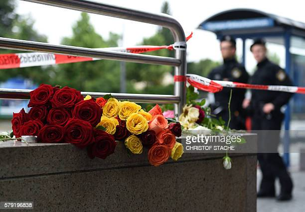 Police officers stand near flowers commemorating victims at the entrance of the subway station near the shopping mall Olympia Einkaufzentrum OEZ in...