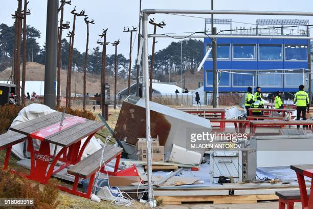TOPSHOT Police officers stand near food stalls that were flown away by strong winds outside the Gangneung Ice Arena in Gangneung during the...