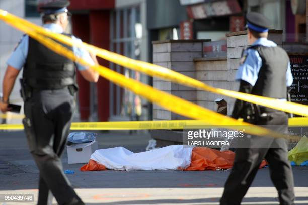 TOPSHOT Police officers stand near one of the bodies on the street after a truck drove up on the curb and hit several pedestrians in Toronto Ontario...