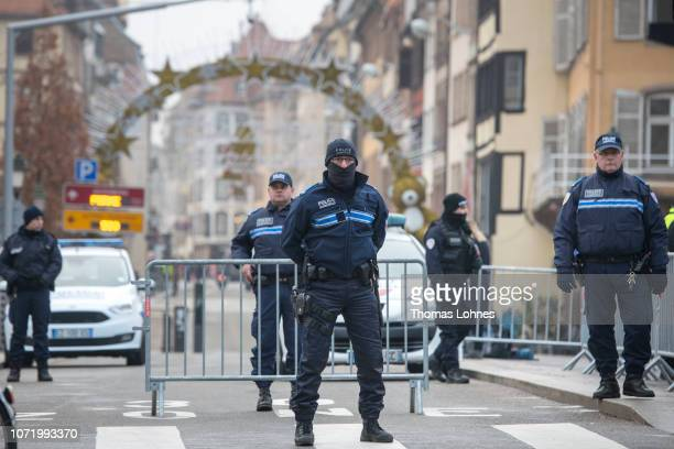 Police officers stand near the Christmas market where the day before a man shot 14 people killing at least three on December 12 2018 in Strasbourg...