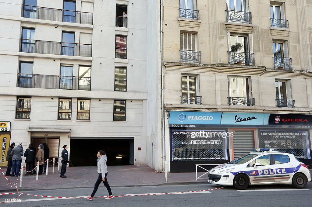 Police officers stand near the entrance of a building garage on February 17, 2013 in Montrouge, a southern Paris suburb, after a 20-year old woman was seriously wounded in her car by gun shots.