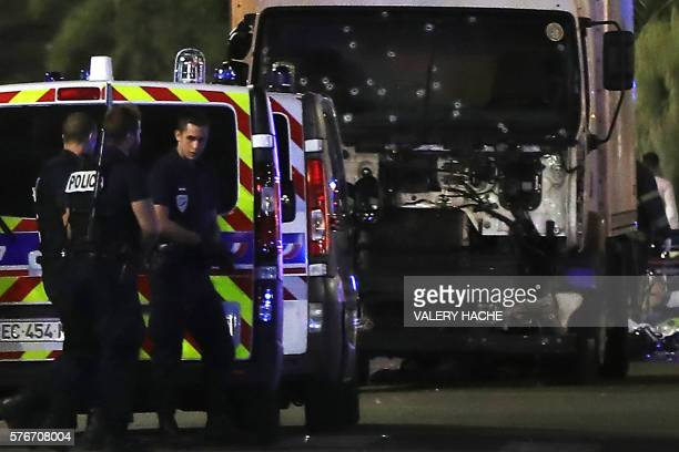 Police officers stand near the truck that ploughed into a crowd leaving a fireworks display in the French Riviera city of Nice on July 14 2016...