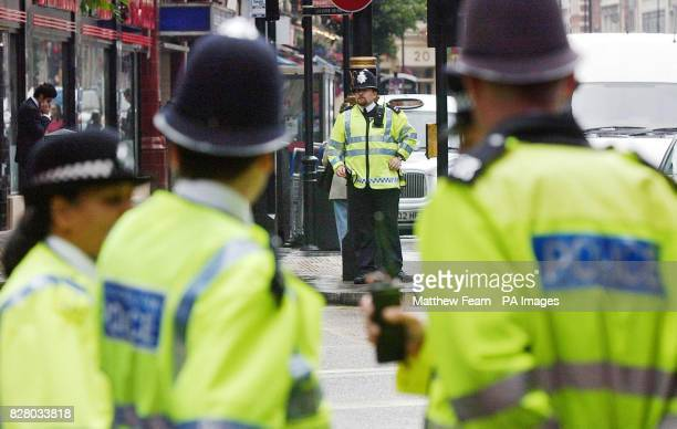 Police officers stand near to Leicester Square underground station on London's Charing Cross Road Police have maintained a policy of high visibility...