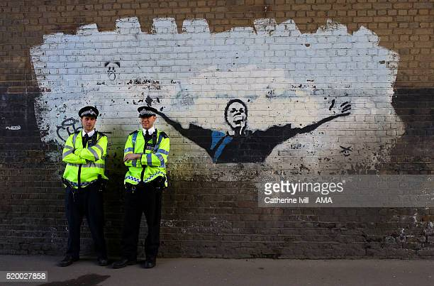 Police officers stand next to a graffiti art mural of former Millwall player and current manager Neil Harris prior the Sky Bet League One match...