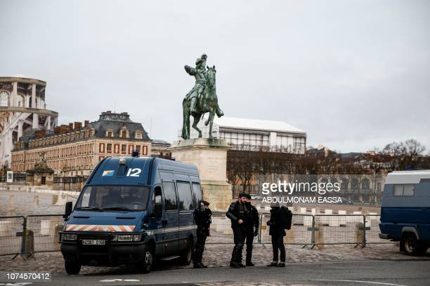 Police officers stand next to a statue of French monarch Louis XIV in a front of the Chateau de Versailles in Versailles outside Paris during a...